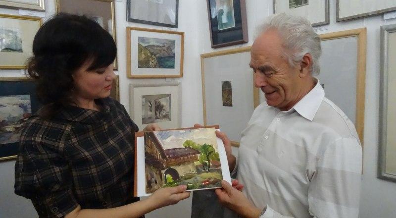 Светлана Глазунова принимает в подарок акварель Якова Басова от сына мастера Александра.