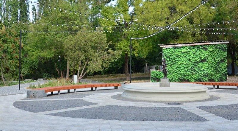 Круглая площадь у восстановленного фонтана «Мальчик с рыбкой», скамьями, необычной гирляндой освещения.