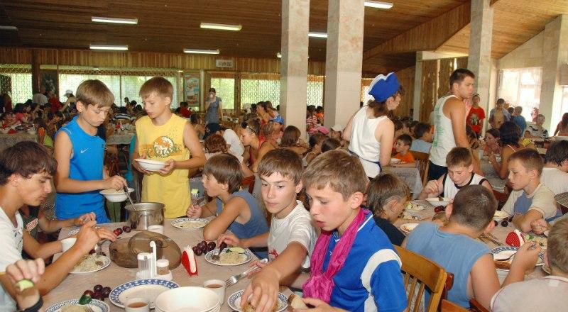Дети из лагеря «Берег» в Алуште обедают в столовой.
