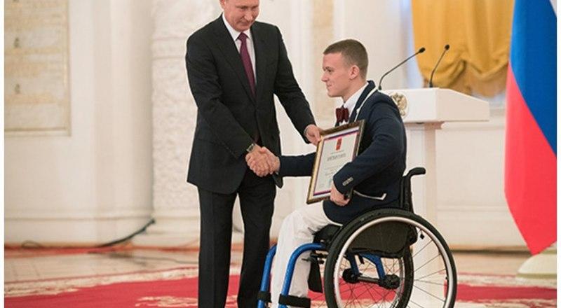 Почётную грамоту правительства страны за успехи в спорте вручает президент Российской Федерации Владимир Путин севастопольскому пловцу паралимпийцу Андрею Граничке.